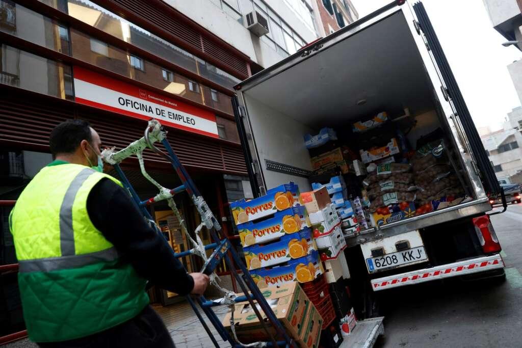 Un hombre descarga un camión justo enfrente de una oficina de empleo./ EFE