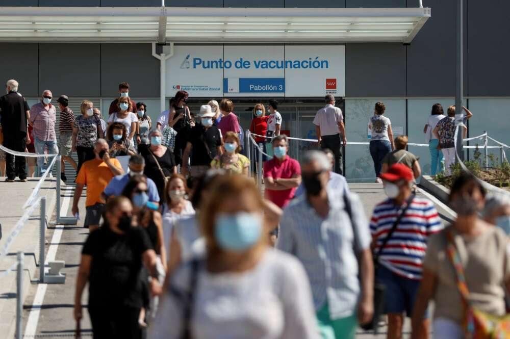 Centenares de ciudadanos llevan más de una hora esperando su turno para vacunarse en el hospital Enfermera Isabel Zendal, algunas refugiadas del sol y de las altas temperaturas bajo sus paraguas, mientras una caravana de coches en los alrededores del centro trata de aparcar. EFE/ Mariscal