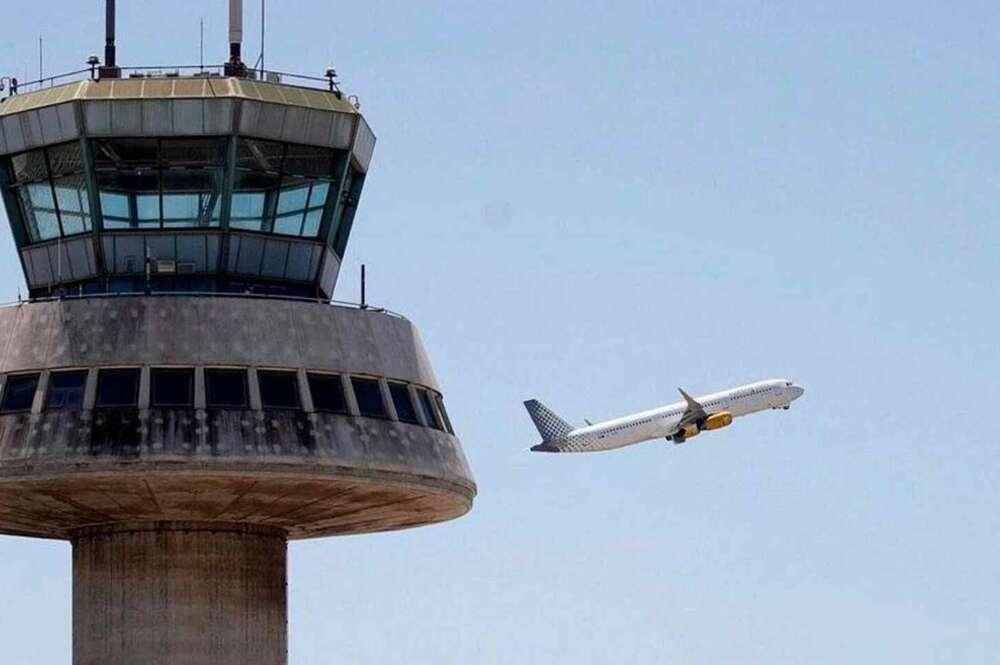 En la imagen, un avión despega ante la torre de control del aeropuerto de El Prat. / EFE